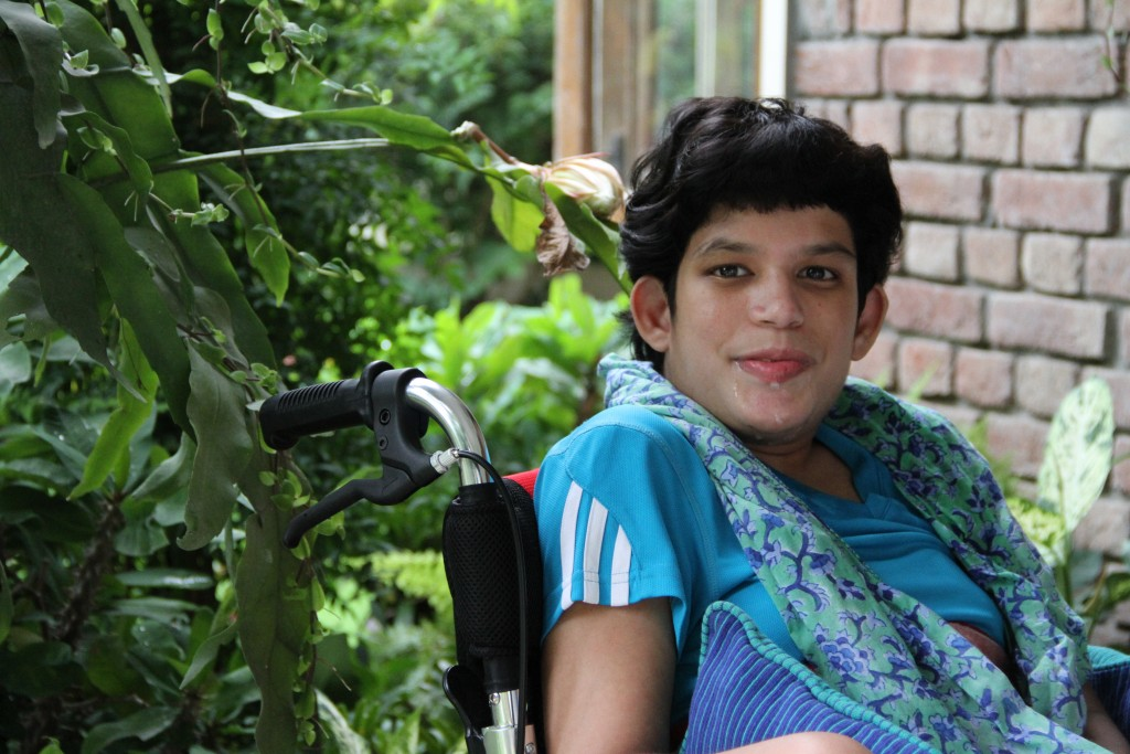 Indian girl in blue sitting in wheelchair with an enigmatic smile.