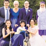 Family Wedding. Bride and groom and family gather round young woman in wheelchair
