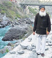 Elderly man in traditional Indian clothes stands beside the river Ganga