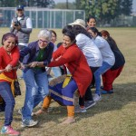 Group of women on one side of a tug-of-war, all laughing and pulling hard