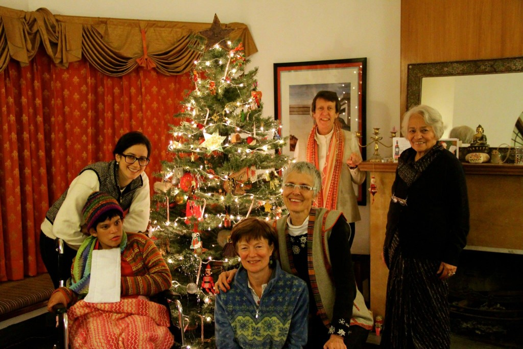 Five women in front of a Christmas tree - one elderly, one in a wheelchair