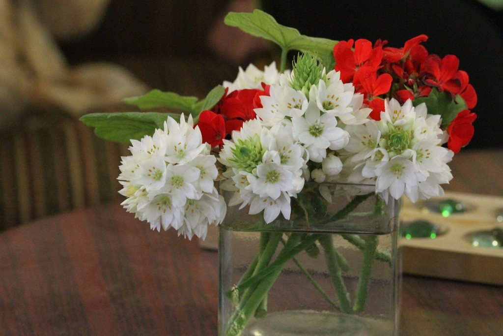 Red and white garden flowers in a square glass vase.