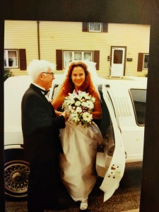 Bride in white gown holding flowers steps out of a white limo, helped by her father