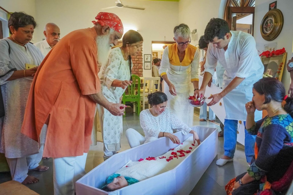 Family gathers around the coffin of a young woman