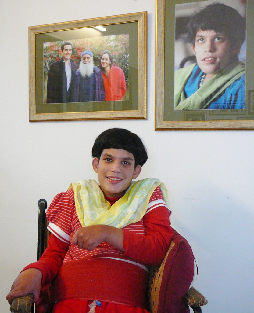 Pretty Indian girl in red, sitting in wheelchair smiling. Background two family photos on the wall.