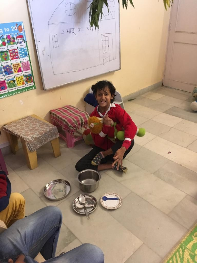 Girl with CP, in red, sitting on floor holding Goldilocks. Small, medium and large bowls lined up in front of her.