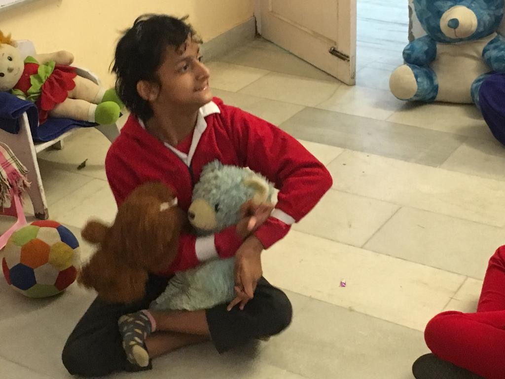Girl with CP in red, sitting on floor holding stuffed bears in her arms