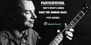 Pete Seeger, American folk singer, playing a guitar. Caption reads: Participation! That's what's gonna save the human race.""