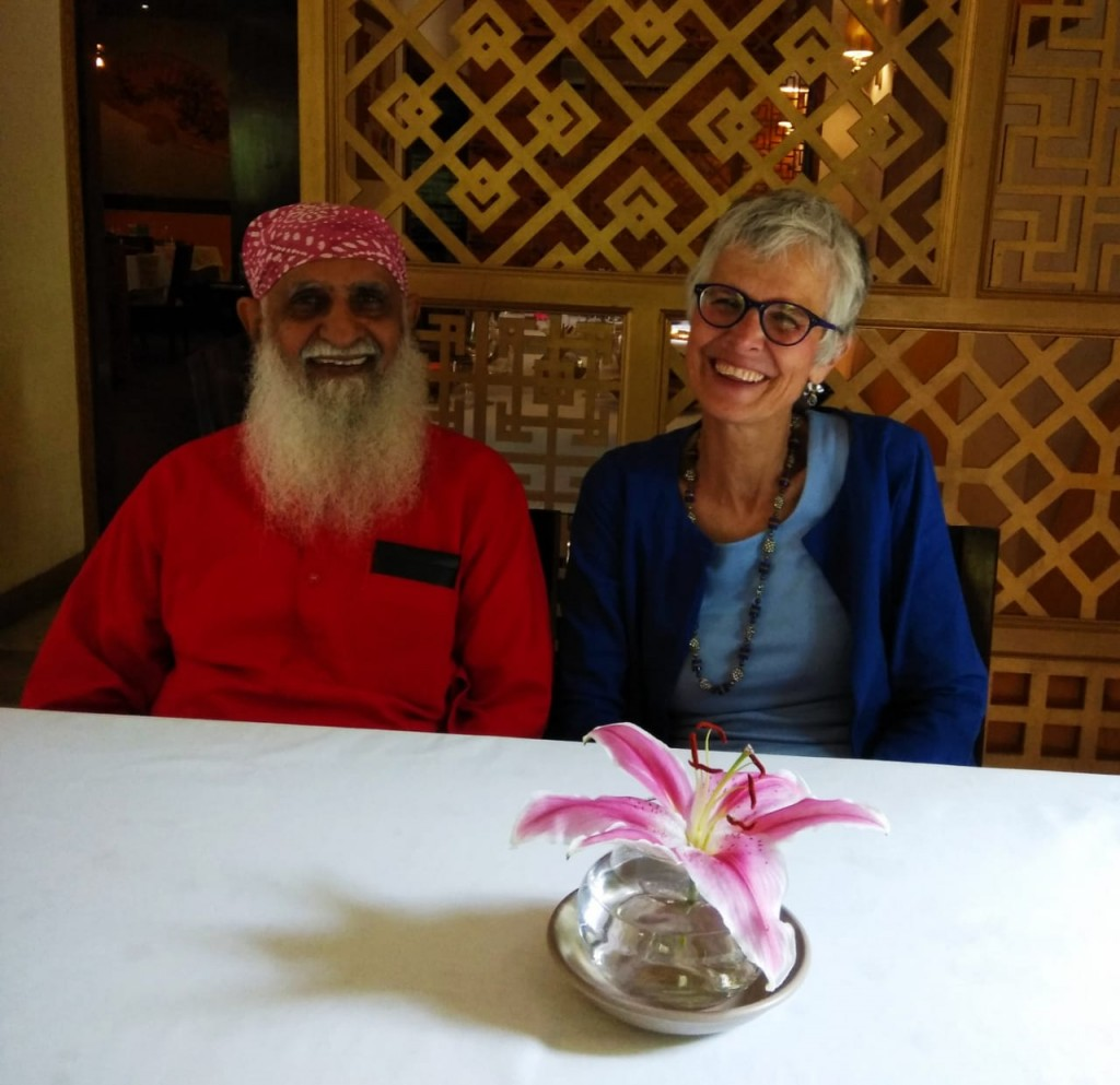 Indian man with redkurta and long white beard; American woman with white hair - both smiling