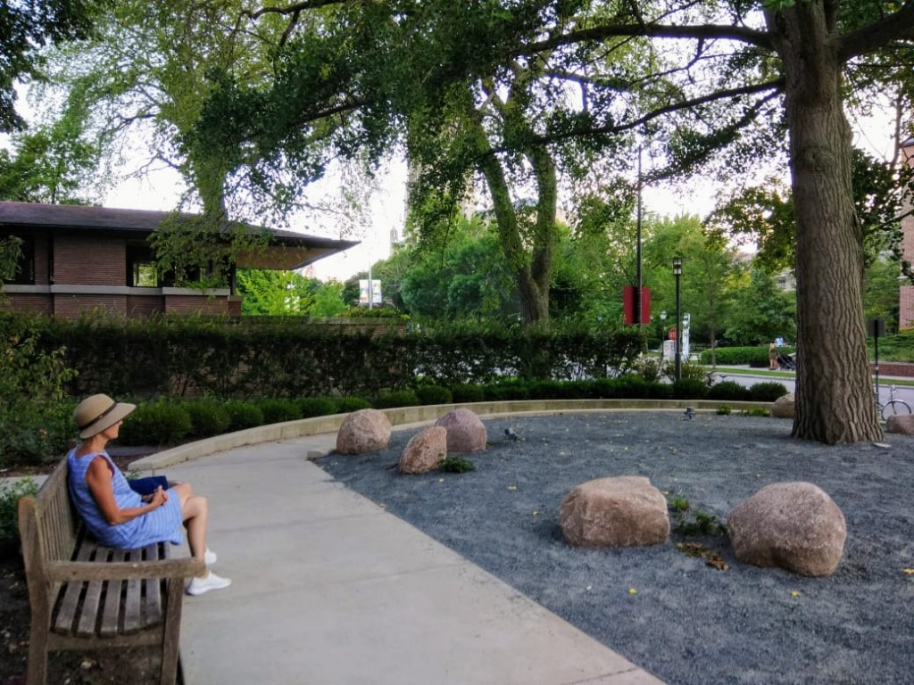 Woman in blue dress and straw hat sitting on a bench, gazing at a rock garden in front of a tree