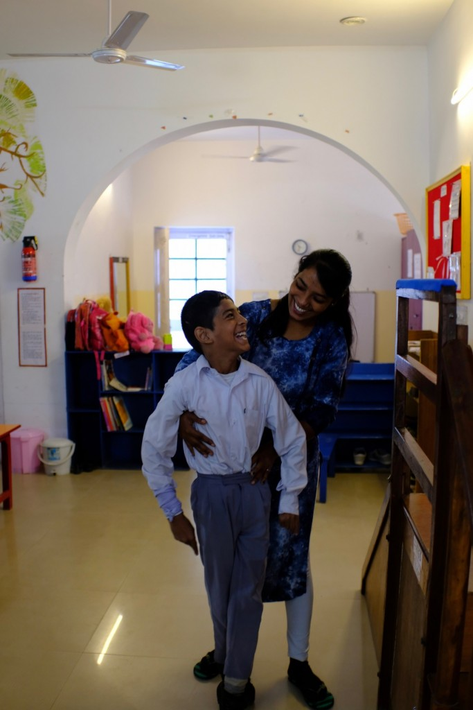 Boy with cerebral palsy being supported to stand by a therapist. Child and adult are smiling at each other.