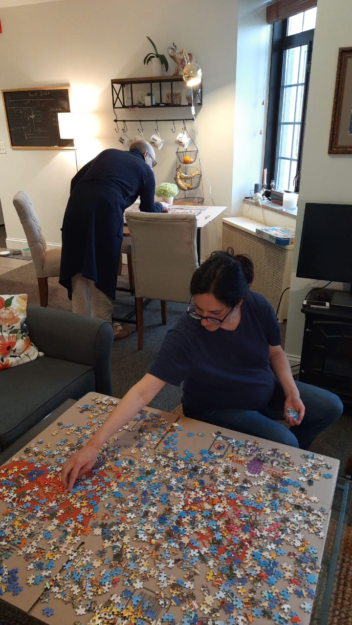 A man with back to camera and woman sitting on a low stool work on a jigsaw puzzle