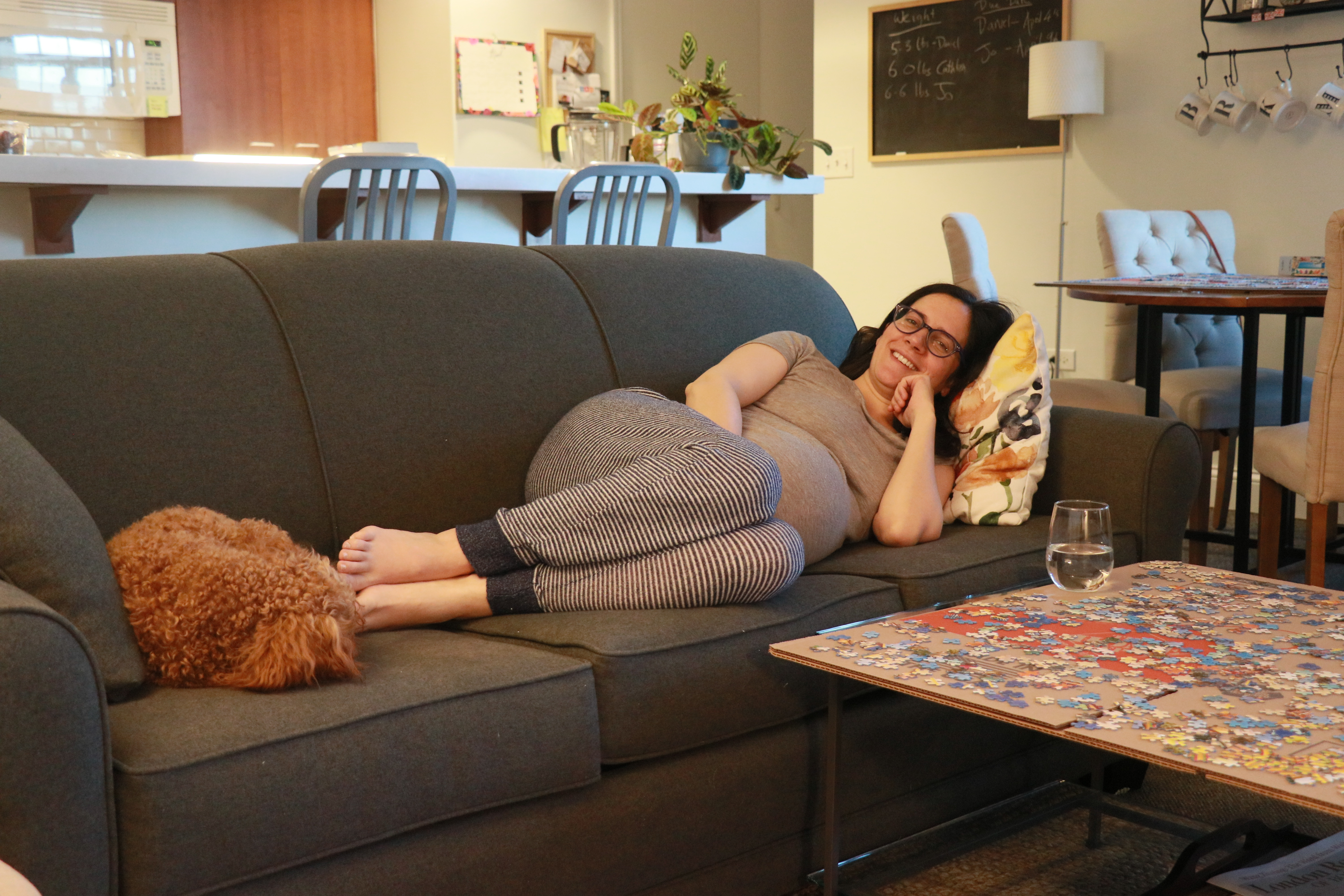 Pregnant woman lying on couch. Puppy at her feet and jigsaw puzzle at her side