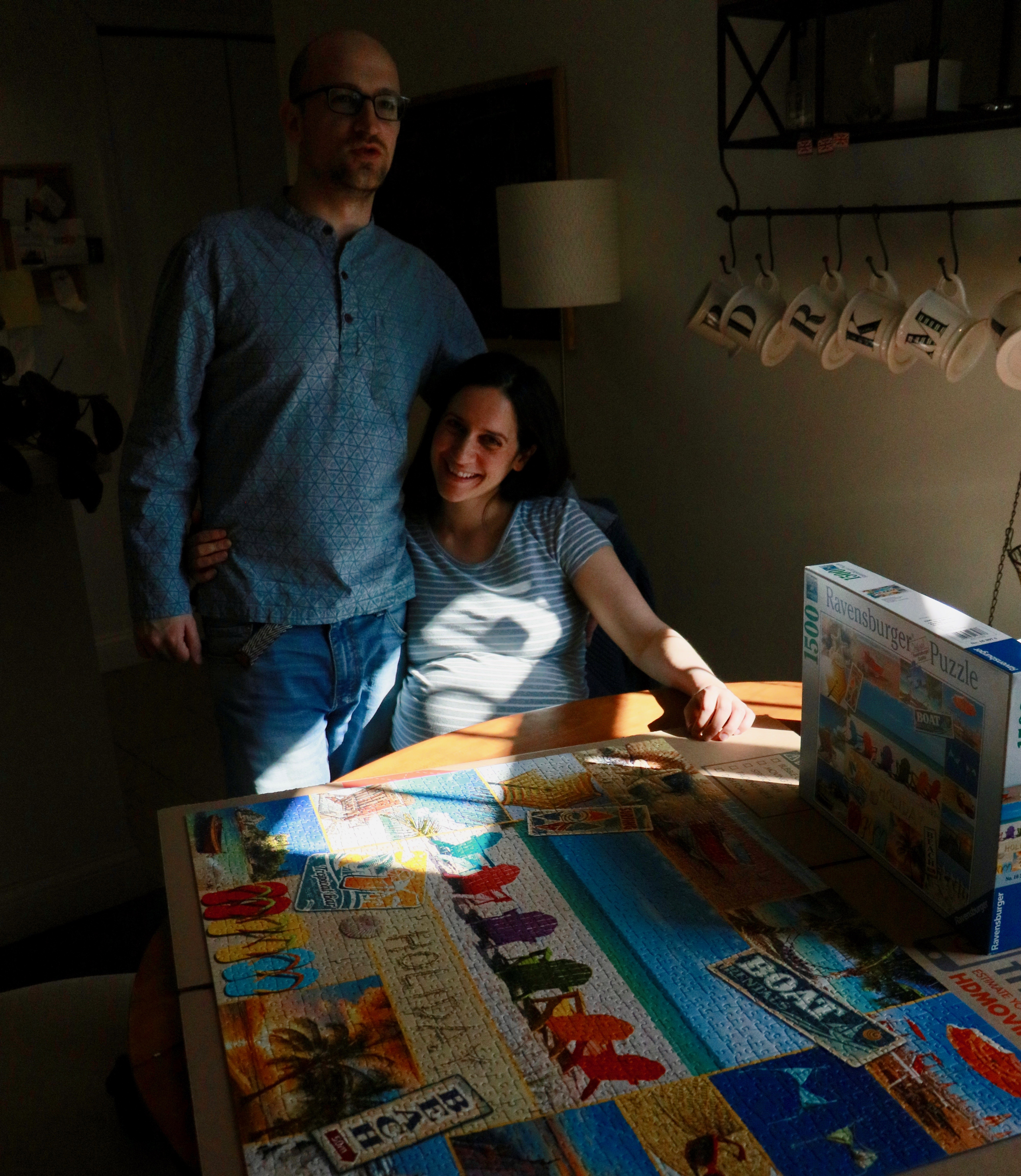 Young couple near jigsaw puzzle in shaft of sunlight