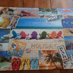 Completed Jigsaw Puzzle of a series of summer images on a wooden table