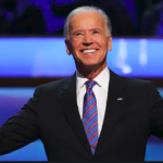 Joe Biden, arms outstretched, beaming smile