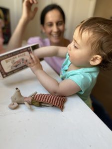 Baby examining a box; Mom in background smiling